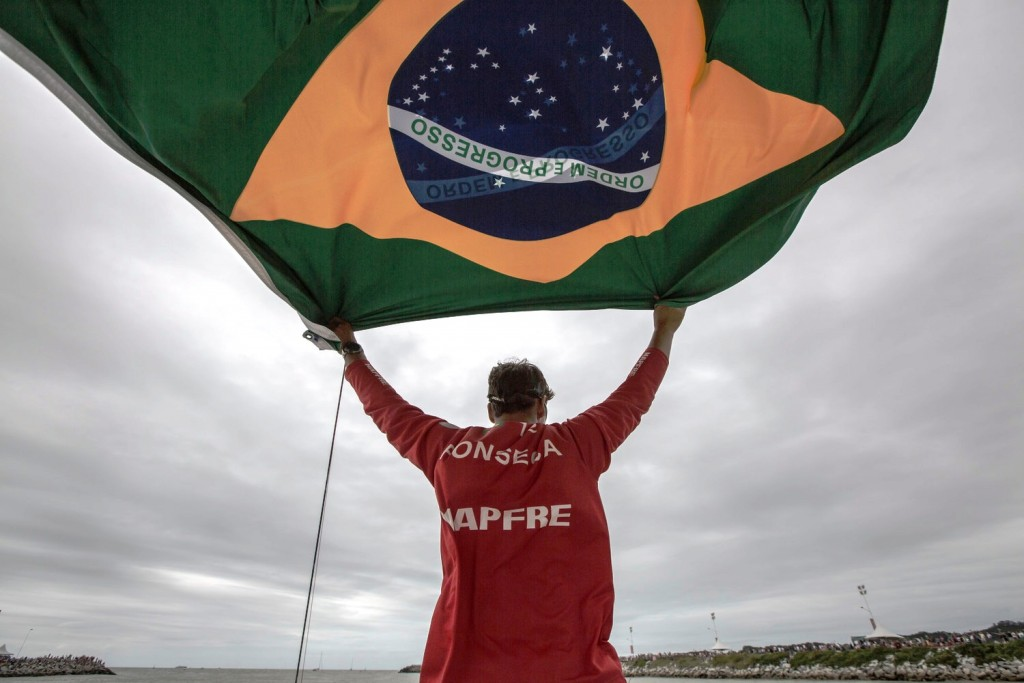 April 19, 2015. Start  of Leg 6 to Newport onboard MAPFRE. Brazilian MAPFRE crew member Andre Fonseca, aka Bochecha, waves the country flag while leaving itaja?.