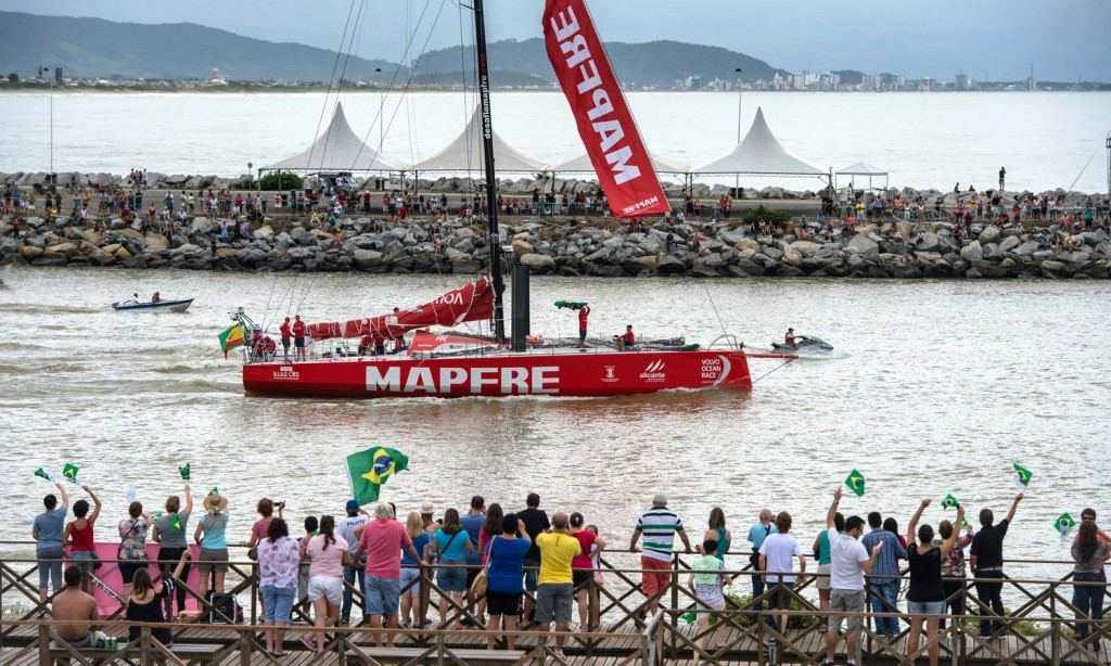 April 19, 2015. Dock out of the start of Leg 6 to Newport. Brazilian MAPFRE crew member, Andre Fonseca, aka Bochecha, waves the crowds with the country flag.